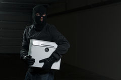 Mail thief. Man wearing black mask holding a mailbox Stock Photos