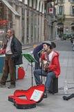 Mailand, Italien - Mai 2017: Der Straßenmusiker spielt Gitarre und singt im Mikrofon Anderer ein Mann vereinbart die Tonausrüstun stockfotografie