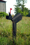 Mailbox. A broken mailbox, with the red flag raised, sitting in an overgrown farmer's field with a barn in the background royalty free stock photos
