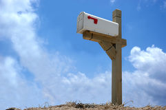 Mailbox. A mailbox mounted on wood stand in clear blue sky background Stock Images