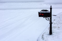 MAilbox. A black mailbox covered with fresh white snow stock image