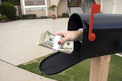 Mailbox and buncle of cash. A bundle of cash is being delivered to a homeowner waiting for an economic stimulus payment or foreclosure bailout Stock Images