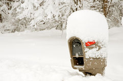 Mailbox covered in deep snow. A roadside rural mailbox covered with deep snow during a winter blizzard Royalty Free Stock Image