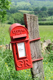 Mailbox in English countryside of Cotswolds. Old mailbox hanging on wood in English countryside of Cotswolds Royalty Free Stock Image