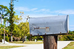 Mailbox with flag down. A grey metal mailbox sitting on a post with the flag down on the side of the road Stock Photo