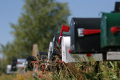 Mailbox flagged. Mailboxes with single one flagged, shallow depth of field with flag as point of focus Stock Photos