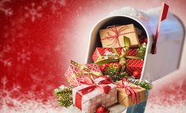 Mailbox full of Christmas presents on red. Mailbox full of Christmas presents. Closeup front view of holiday decorated gift boxes with surprises. Mary Christmas royalty free stock photo