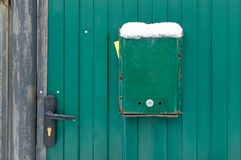 The mailbox is green next to the wicket house. Gates of the house with a lock stock photo