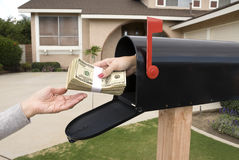 Mailbox handing over money. A bundle of cash is being delivered to a homeowner waiting for an economic stimulus payment or property bailout money Royalty Free Stock Photography