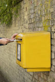 Mailbox. Man's hands posting a letter in a yellow post box, stone wall background Royalty Free Stock Images
