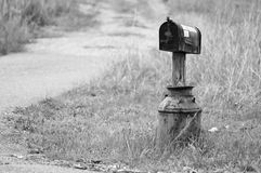 Mailbox In A Milk Jug. An old Milk Jug is used as a base for this mailbox along a rural dirt road Stock Photos