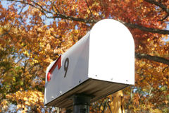 Mailbox in November. White mailbox outdoors with the number 9 on the side. Autumn trees provide a colorful background on a November afternoon Stock Images