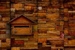 A mailbox on an old stone wall, Old wooden mailbox. Royalty Free Stock Image