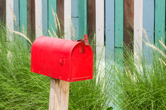 Mailbox. A plain Red Mailbox in front of some bushes stock photos