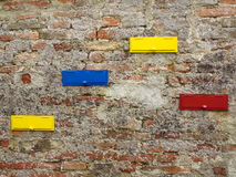 Mailbox slots on brick wall background. A red brick wall with four colorful mailbox slots Stock Images
