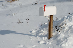 Mailbox in Snow. A white mailbox with the red flag up after a snow storm Royalty Free Stock Images
