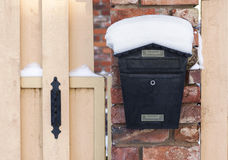 Mailbox at winter. Black mailbox covered with snow outside residential house Stock Image