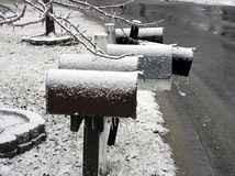 Mailboxes. Snow and ice covered mailboxes sit in the dead of winter frozen to the wind and elements Stock Photo