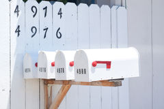 Mailboxes in front of white fence Royalty Free Stock Image