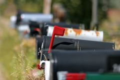 Mailboxes - you have mail. Mailboxes lined up, flagged box as object of focus Stock Photography