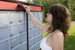 Mailing a letter. Woman mailing a letter outside Stock Photo