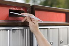 Mailing a letter. Closeup of woman`s hand mailing a letter Stock Image