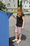 Mailing Letter. Girl putting letter in large blue post box Royalty Free Stock Photos