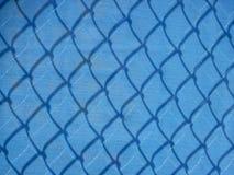 Maille bleue clôturant avec des ombres Photographie stock libre de droits