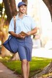 Mailman που περπατά κατά μήκος της οδού που παραδίδει τις επιστολές Στοκ φωτογραφία με δικαίωμα ελεύθερης χρήσης