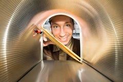 Mailman που τοποθετεί την άποψη φακέλων από μέσα από την ταχυδρομική θυρίδα Στοκ εικόνα με δικαίωμα ελεύθερης χρήσης