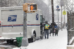 Mailman delivers package in snow storm. BRONX, NEW YORK - JANUARY 7: Mail man delivers mail in snow storm.  Taken January 7, 2017 in New York Stock Images