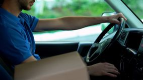 Mailman driving car, cardboard box standing near him, parcels express delivery. Stock photo stock images