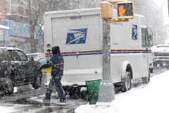 Mailman with package during snow storm Stock Photo