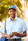 Mailman Walking Along Street Delivering Letters Stock Images