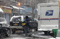 Mailman working during snow storm in the County of the Bronx. BRONX, NEW YORK - JANUARY 7:  Mailman carries package for delivery during snow storm.  Taken Royalty Free Stock Images