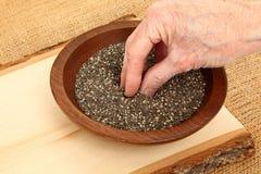 Main à l'intérieur de cuvette de Chia Seeds Photos stock