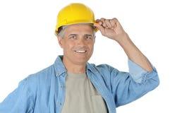 Main âgée moyenne de travailleur de la construction sur le casque antichoc Images libres de droits