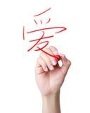 Main écrivant l'amour de Hanzi de Chinois Image libre de droits