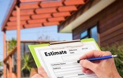 Main écrivant une évaluation pour la construction à la maison Renovat Photos libres de droits
