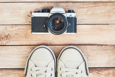 Main accessories of hipster photographer. Photo camera and shoes. Top view of accessories for travel, photo camera and shoes Stock Photography