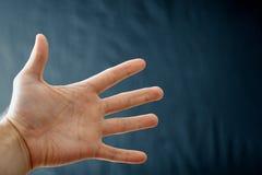 Main adulte avec le syndrome de Raynaud - phénomène Main haute étroite avec des doigts sur le fond foncé avec l'espace de copie photo stock