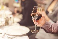 Main adulte tenant le verre du gémissement rouge Grillage à la célébration Café ou fond de restaurant Discours en chef tandis que Photo stock