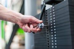 Main ajustant des poids au centre de fitness image libre de droits