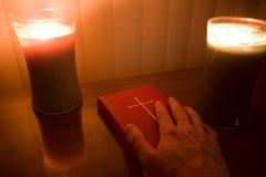 Main allumée par bougie sur la bible Photo stock