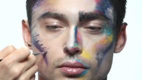Main appliquant le maquillage artistique banque de vidéos