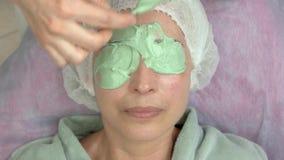 Main appliquant le masque protecteur d'alginate banque de vidéos