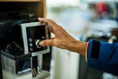 Main appuyant sur le bouton de la machine de café images libres de droits
