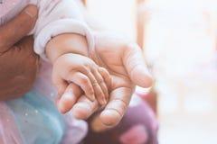 Main asiatique de bébé tenant sa main de grand-mère avec amour Photographie stock libre de droits