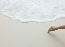 Main asiatique de femme tenant la pierre de mer blanche au coin sur la plage blanche propre et vide de sable avec la vague de mer Images stock