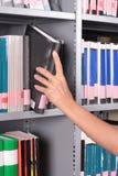 Main atteignant pour le livre sur une étagère photos libres de droits